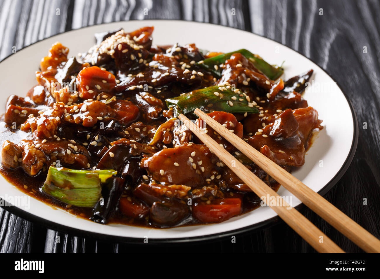 Portion of roast pork with mun mushrooms and vegetables in a sweet and sour sauce closeup on a plate on the table. horizontal - Stock Image