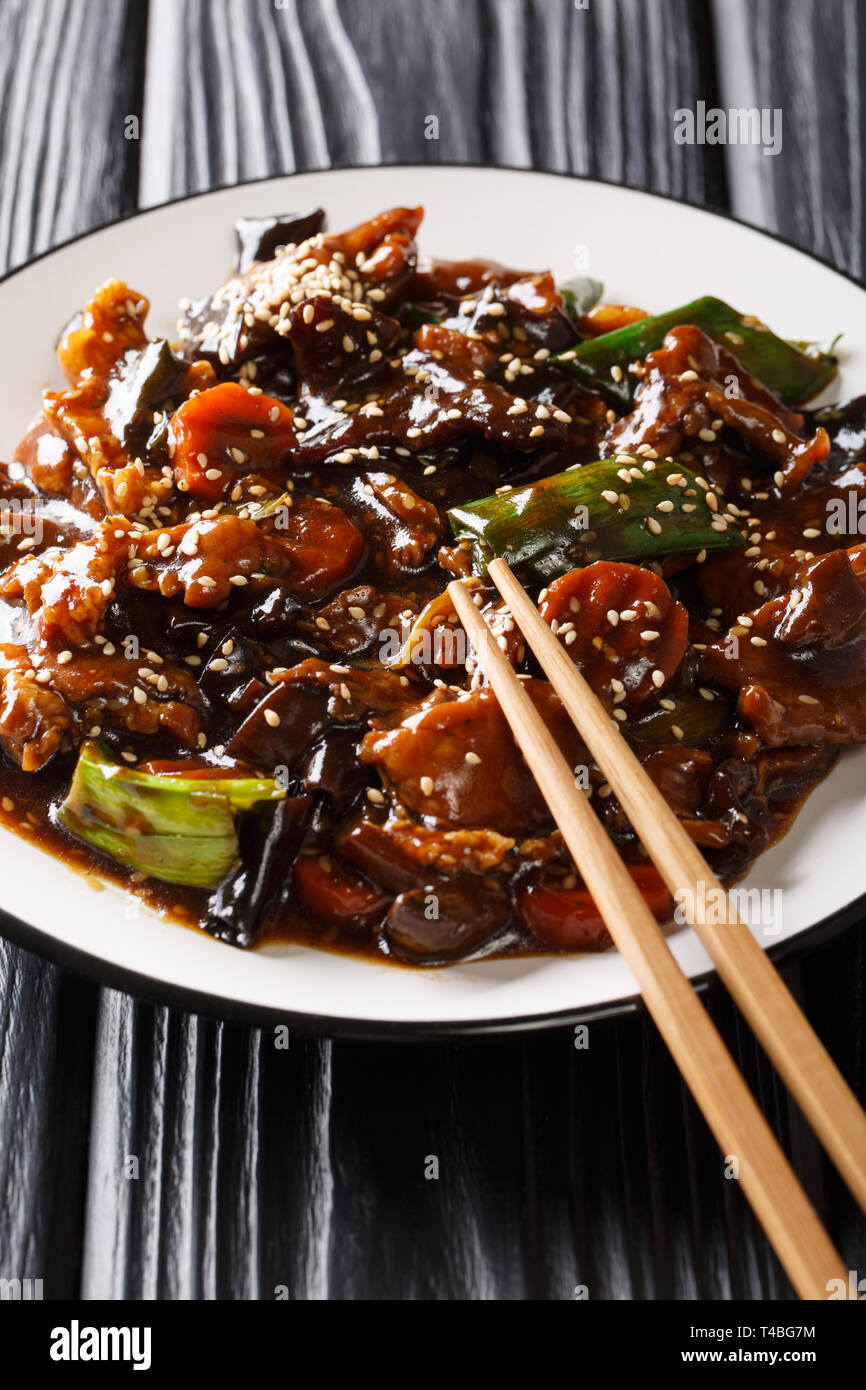 Chinese delicious stir fry pork with mun mushrooms and vegetables close-up on a plate on the table. vertical - Stock Image