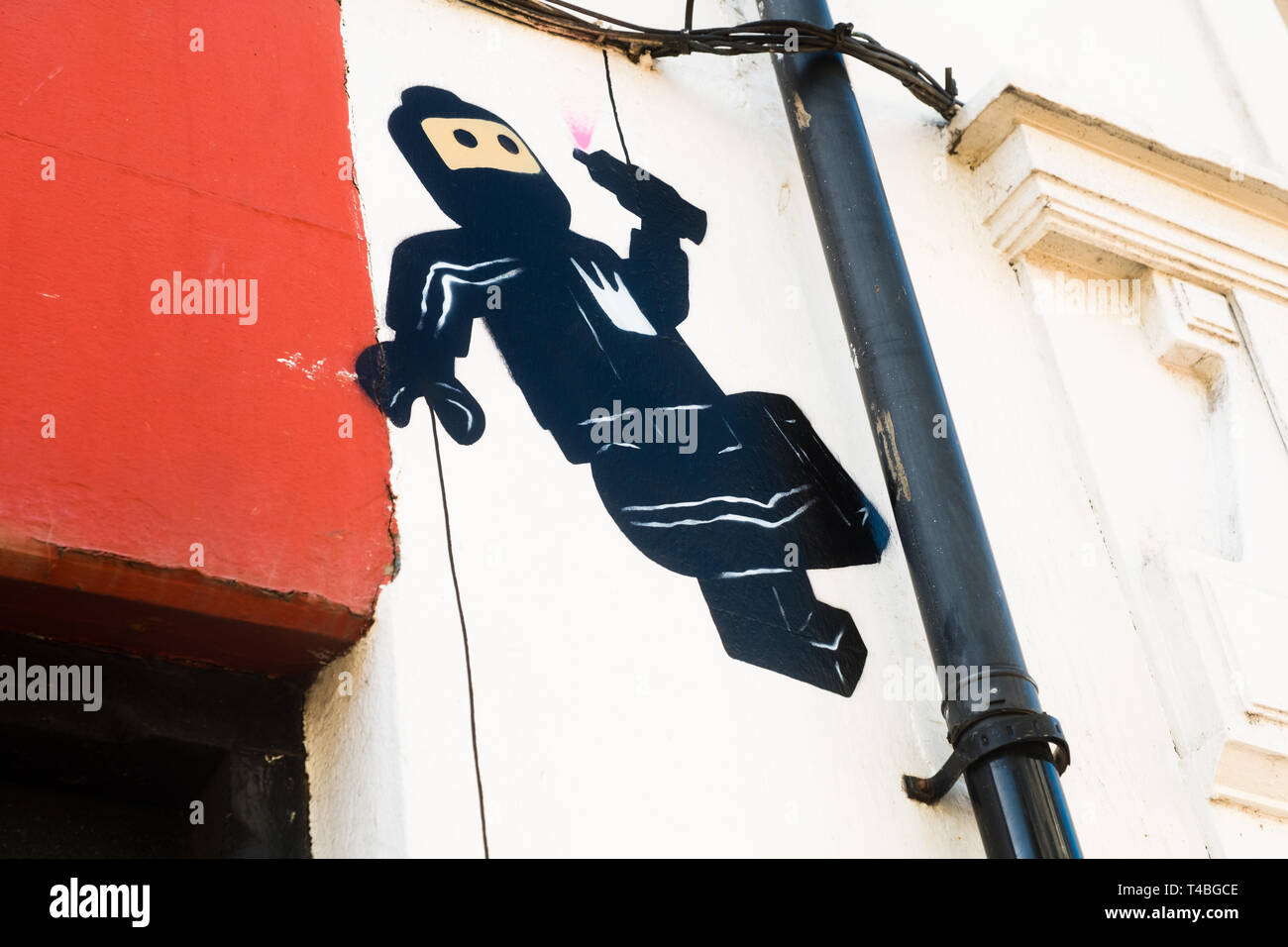 Graffiti by James Ame - Ame72 (The `Lego Guy)  -  on a wall in Aberystwyth showing a black  suited 'ninja' character apparently  falling off a drainpipe holding a can of spray paint after painting a pink heart on the wall. March 10 2019 - Stock Image