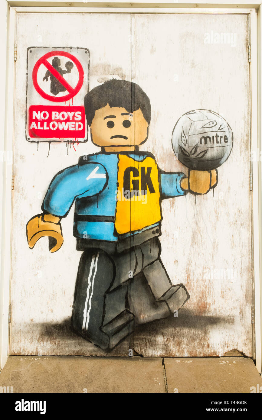 """""""No Boys Allowed"""" Graffiti by James Ame - Ame72 (The `Lego Guy)  -  on the exterior of the leisure centre in Aberystwyth, showing an unhappy boy in a GK  netball vest, in reference to the ban by the Urdd ( a welsh langiage youth organisation) on boys competing in netball competitions.  March 10 2019 Stock Photo"""