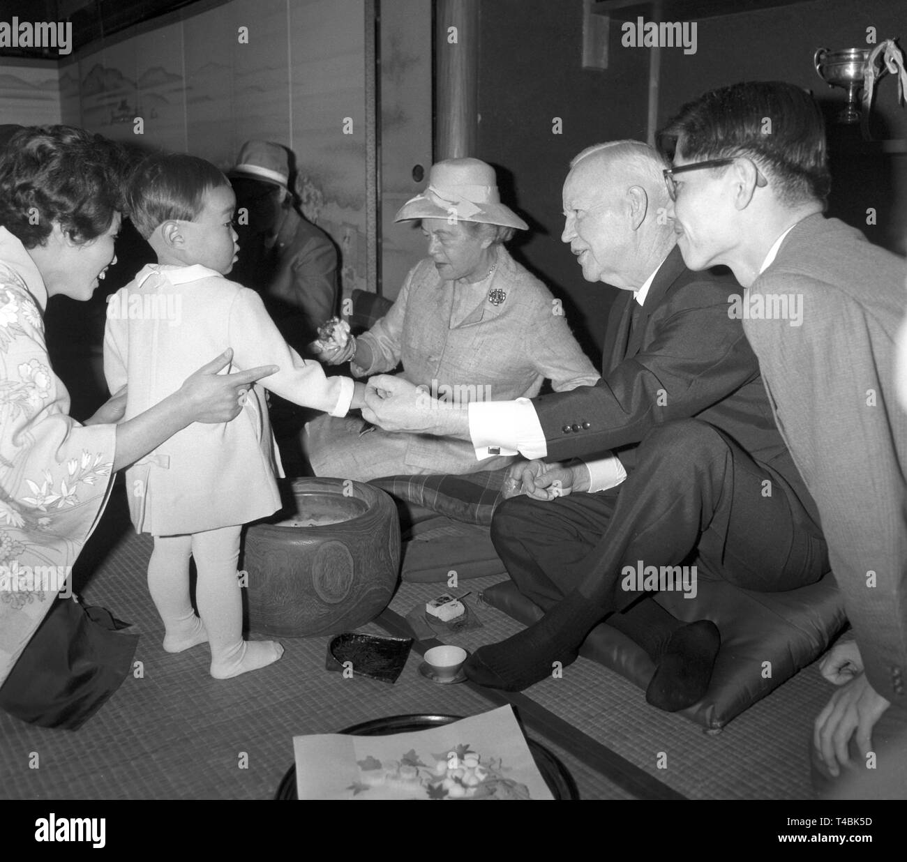During their visit of the ancient imperial city Kyoto, the federal president Heinrich Lübke (2nd from the right) and his wife (3rd from the right) participate in a tea ceremony without wearing shoes and in a Japanese sitting posture, while a little child is welcoming Heinrich Lübke. | usage worldwide - Stock Image