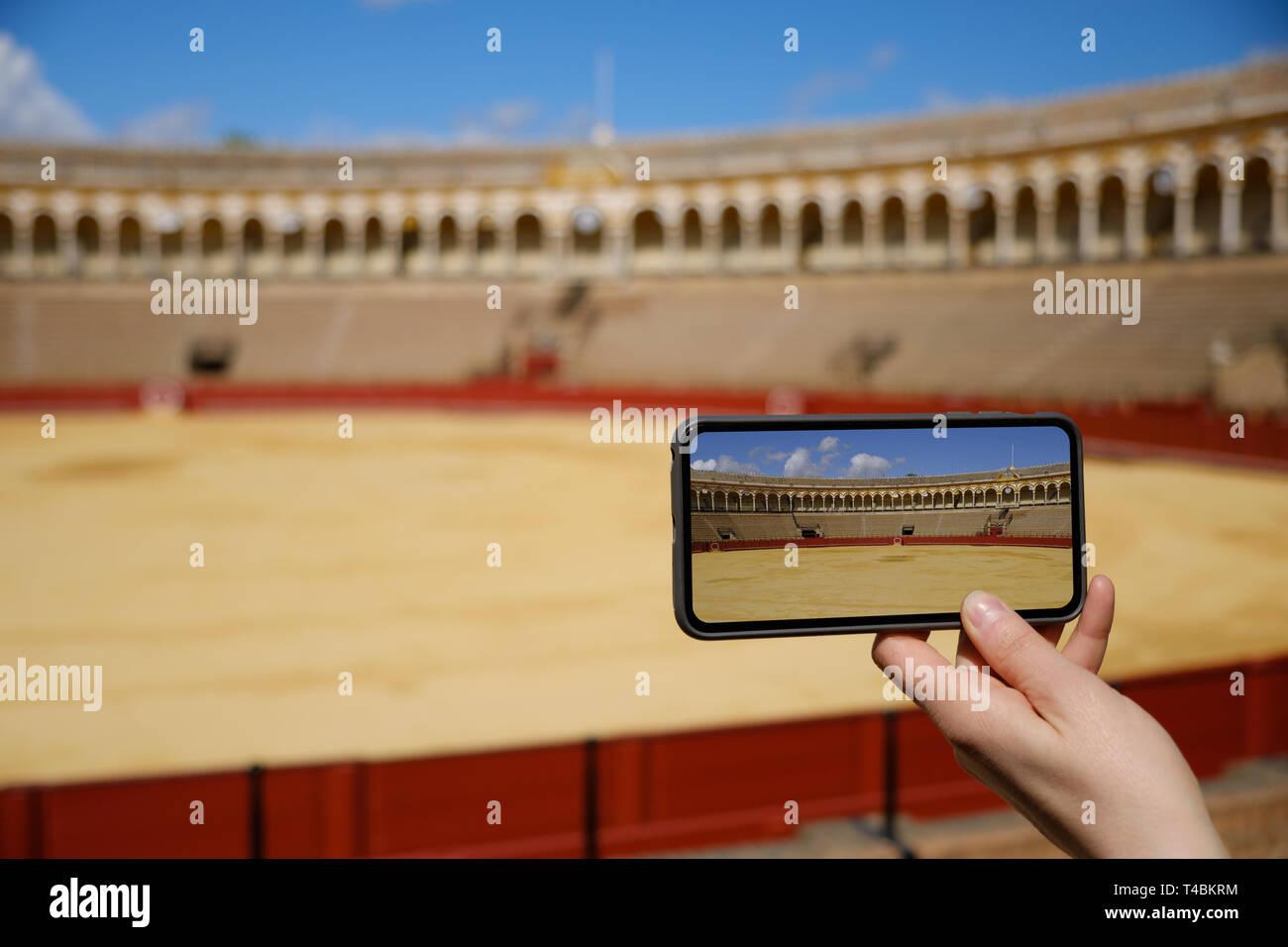woman hand take a photo with smart phone to Bullfighting arena (plaza de toros) in Seville, Real Maestranza de Caballeria de Sevilla, Spain - April 20 - Stock Image