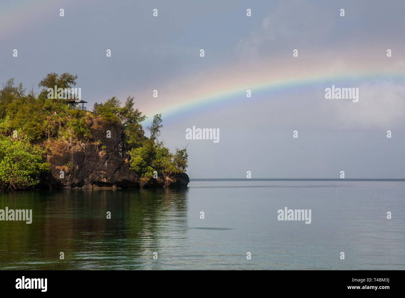 A beautiful rainbow appears over the western lagoon in the Republic of Palau. This Micronesian island-nation is known for its scuba diving. - Stock Image