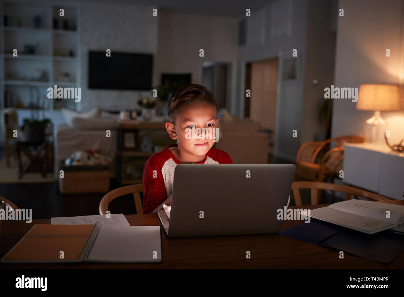 Pre-teen Hispanic boy sitting at dining table doing his homework using a laptop computer, front view - Stock Image