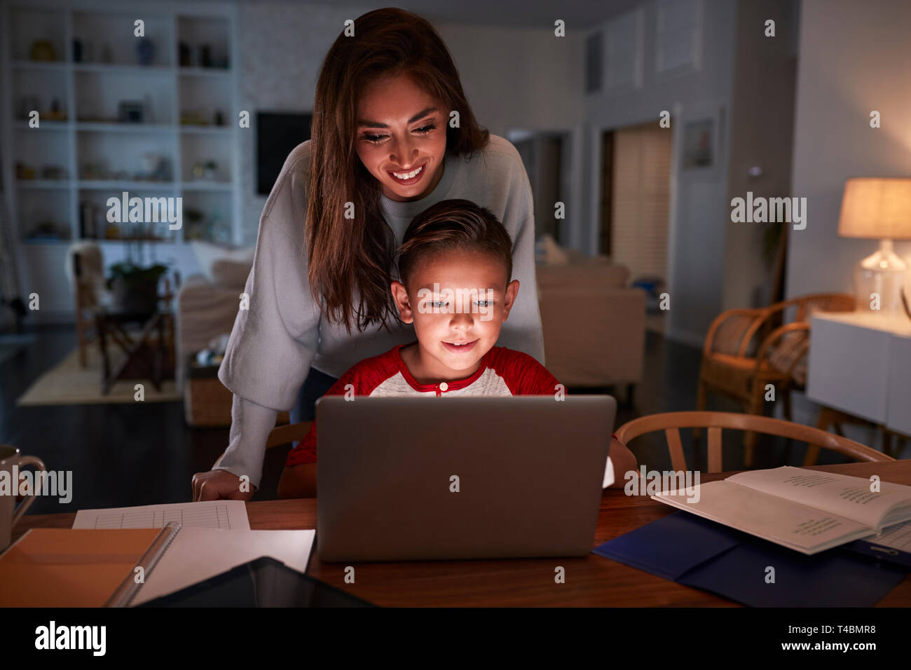 Hispanic woman looking over her son's shoulder while he does his homework using laptop computer Stock Photo