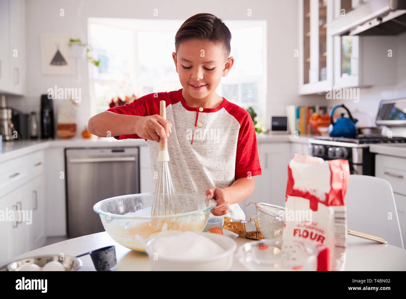 Pre-teen boy making a cake in the kitchen mixing cake mix, smiling, close up - Stock Image