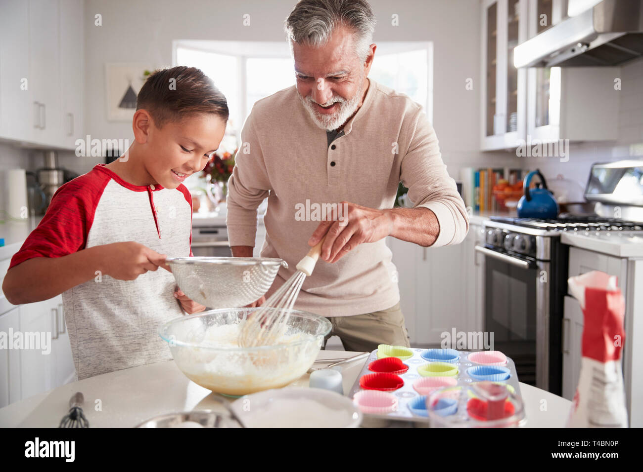 Pre-teen boy making cake mixture in the kitchen with his grandfather, close up - Stock Image