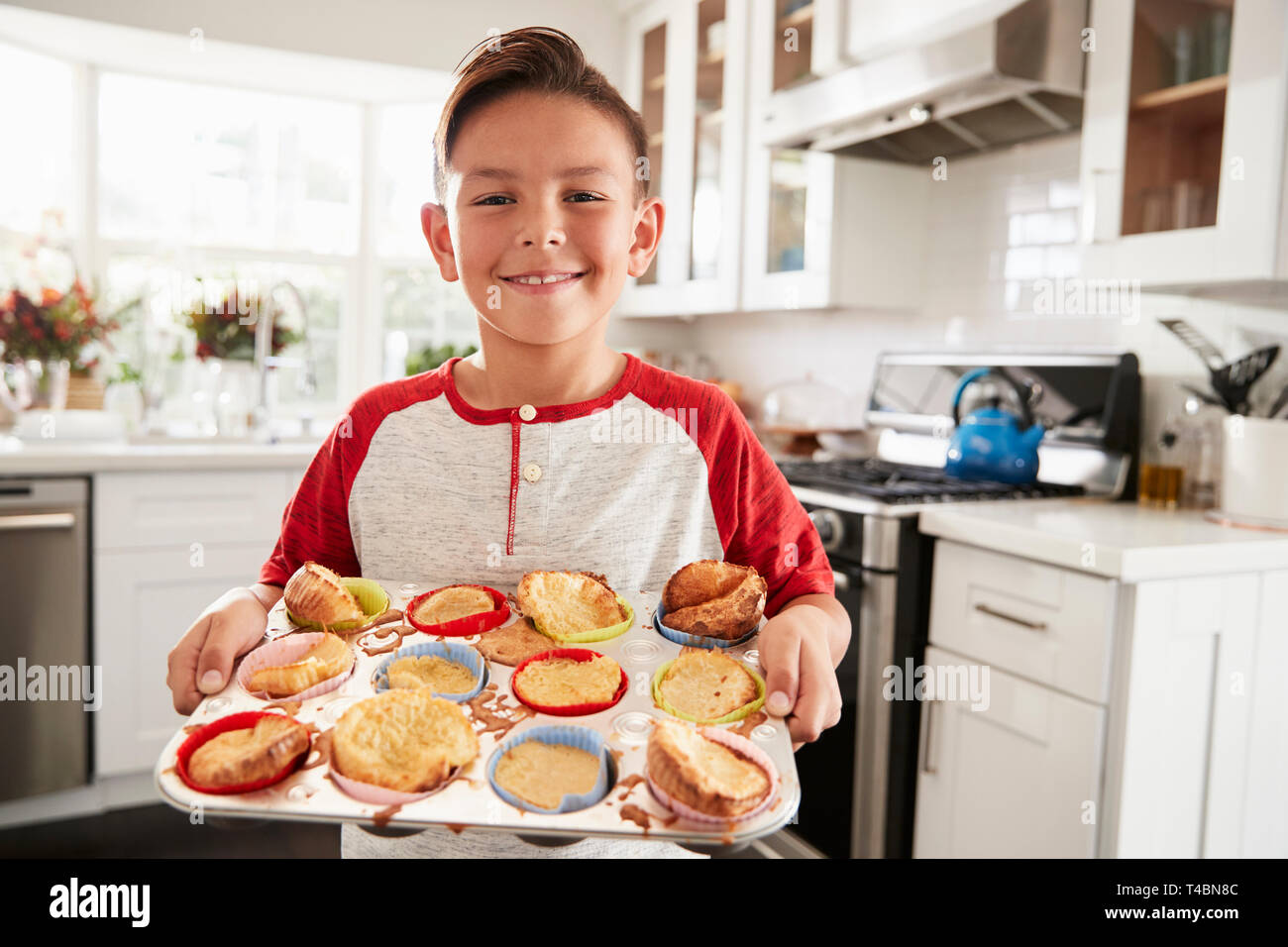 Proud pre-teen Hispanic boy standing in kitchen presenting the cakes he's made to camera, close up - Stock Image