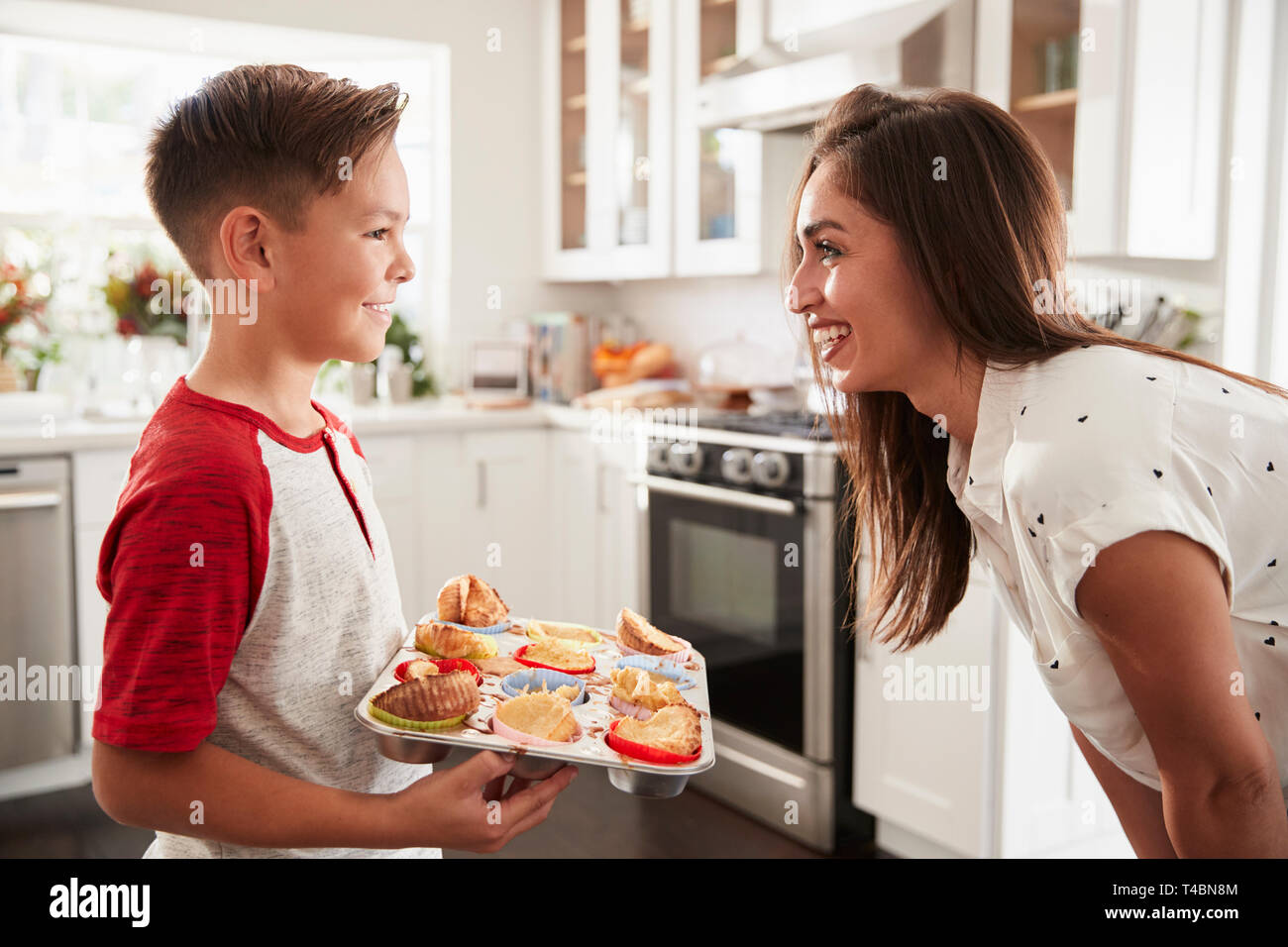 Pre-teen Hispanic boy presenting the cakes he has baked to his proud mother, close up - Stock Image