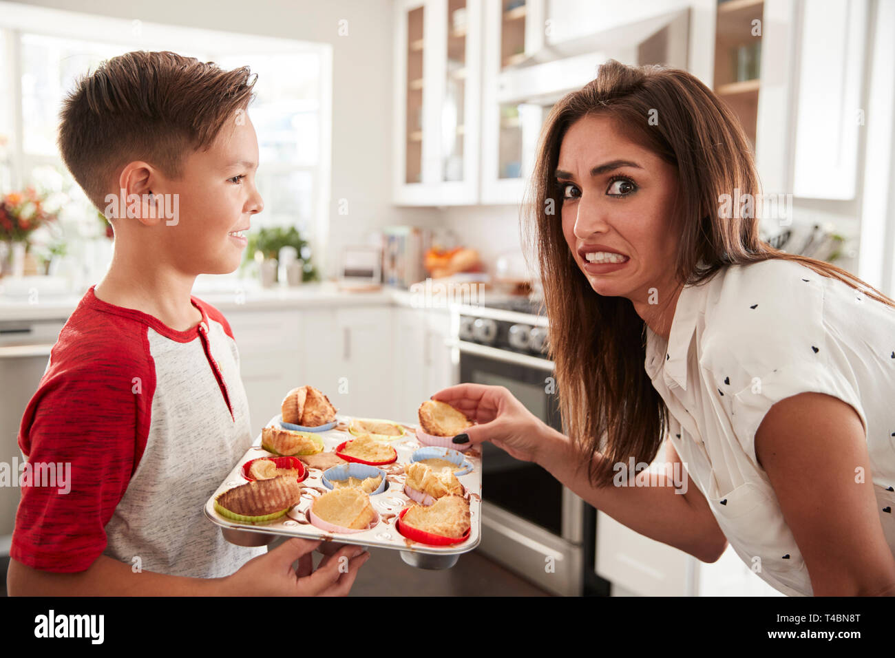 Pre-teen Hispanic boy presenting the cakes he has baked to his disappointed mother, close up - Stock Image