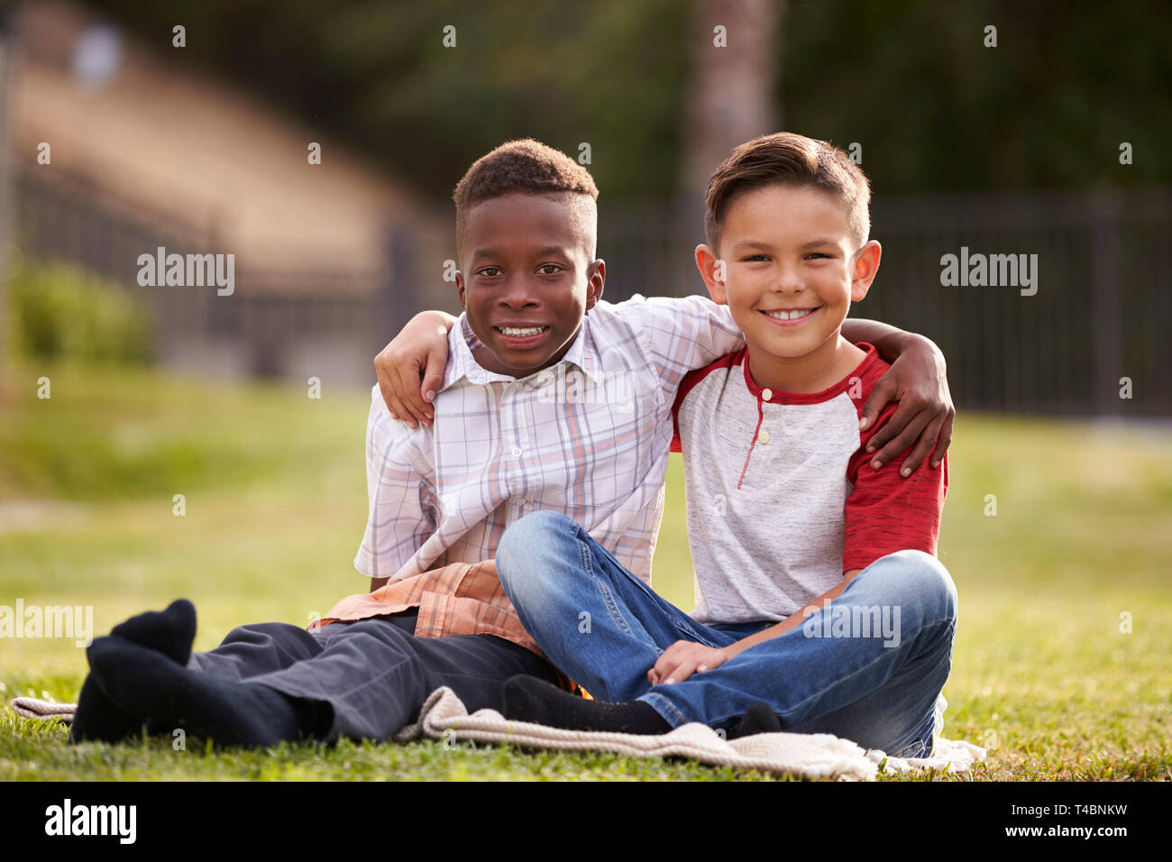 Two pre-teen male friends sitting on the grass in a park, arms around each other, looking to camera - Stock Image