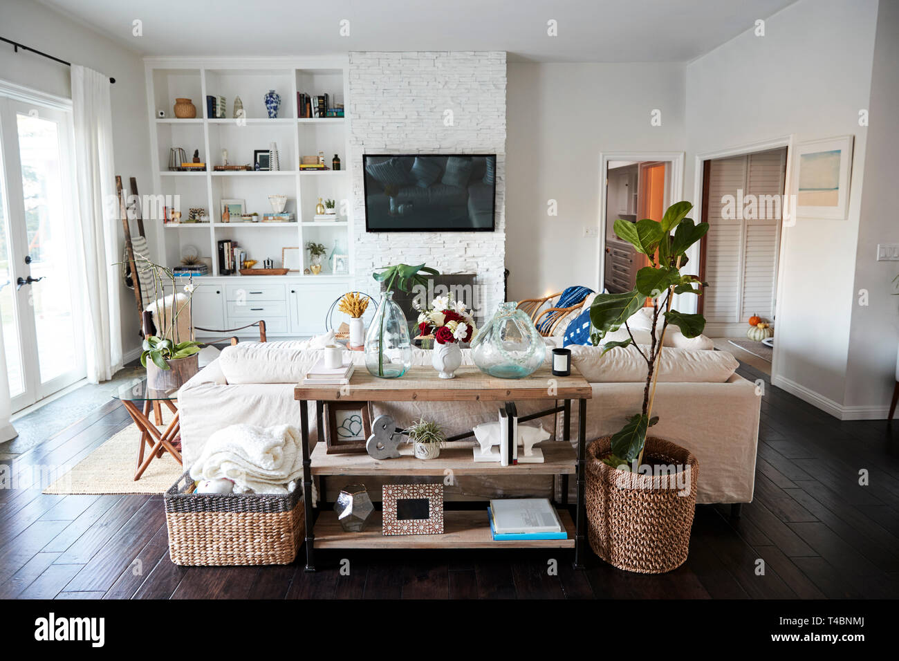 A Family Living Room With White Walls And Dark Wood Floorboards Seen In Daylight From Behind The Sofa Which Sits In A Central Position No People In Shot Stock Photo Alamy
