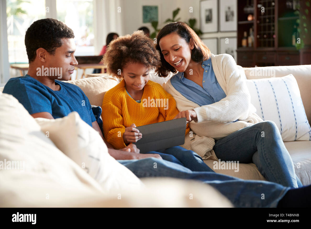 Young parents and their pre-teen daughter sitting on a sofa in the living room using a tablet computer together, selective focus - Stock Image