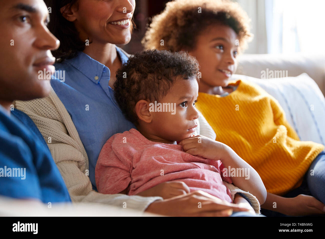 Close up of children sitting on the sofa in their living room watching TV with their parents, side view Stock Photo