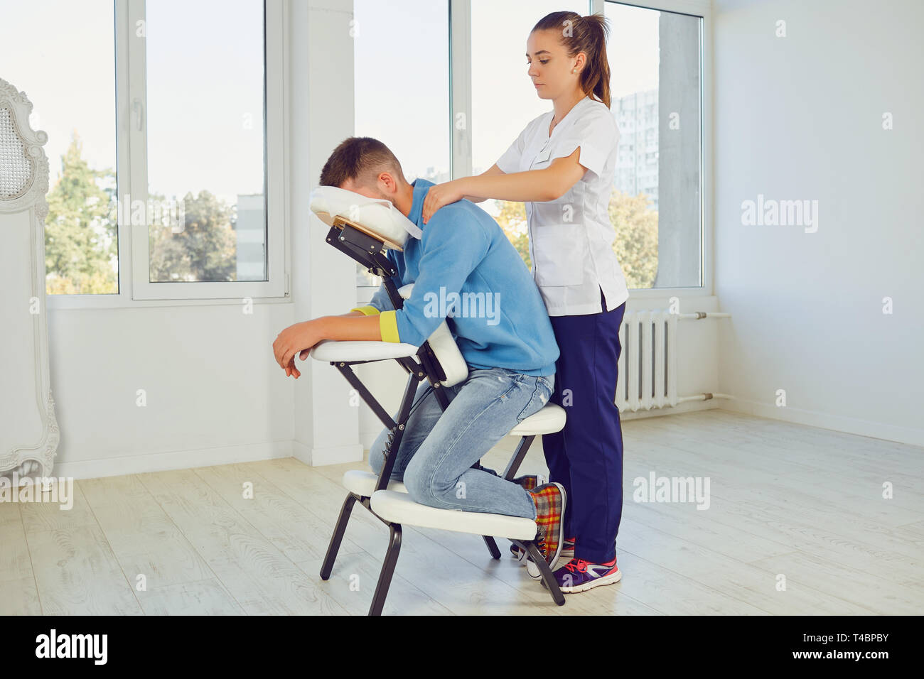 Woman massaging man in special stand - Stock Image