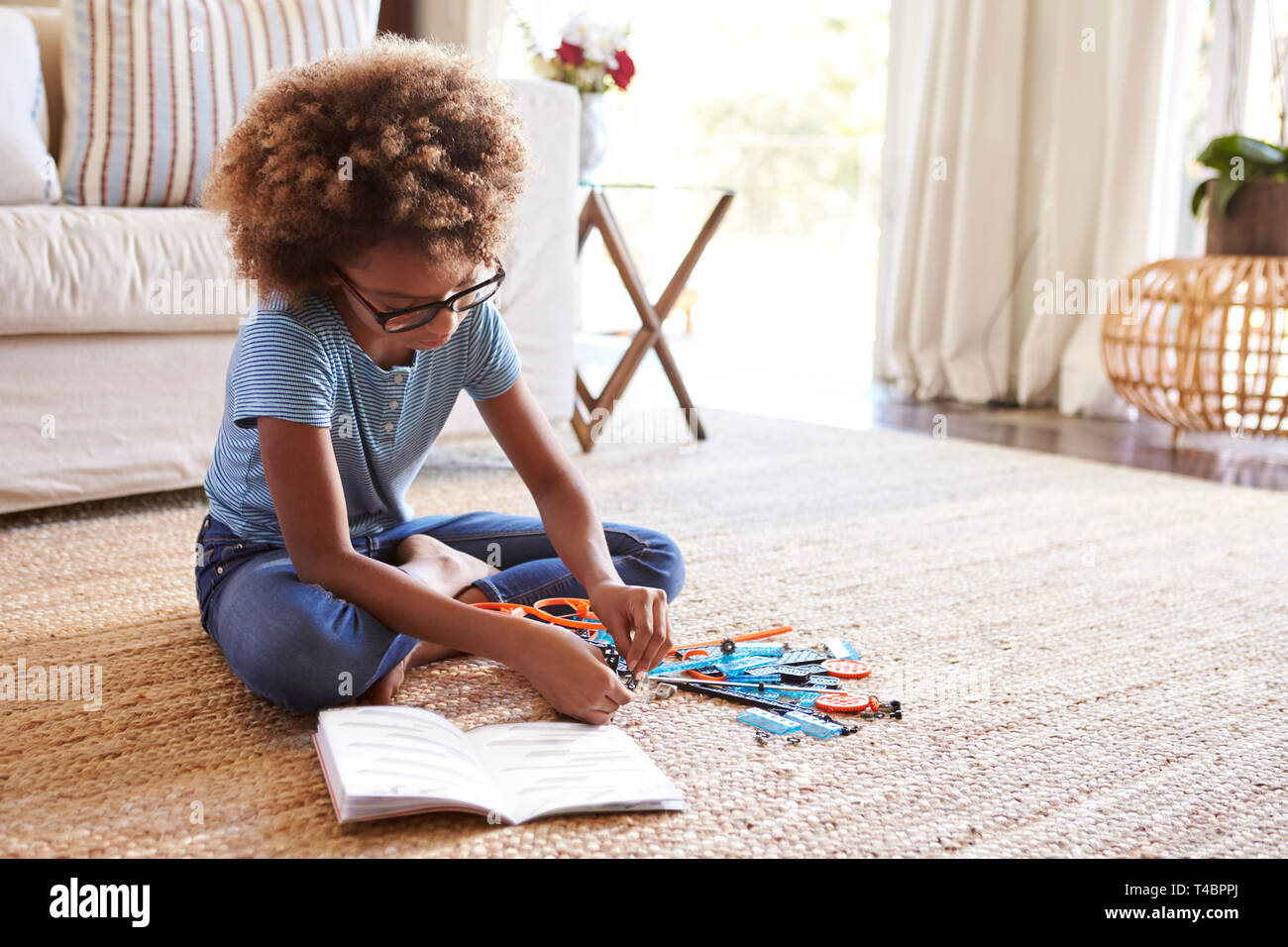 Pre-teen girl sitting on the floor in the living room reading instructions and constructing a model, close up - Stock Image