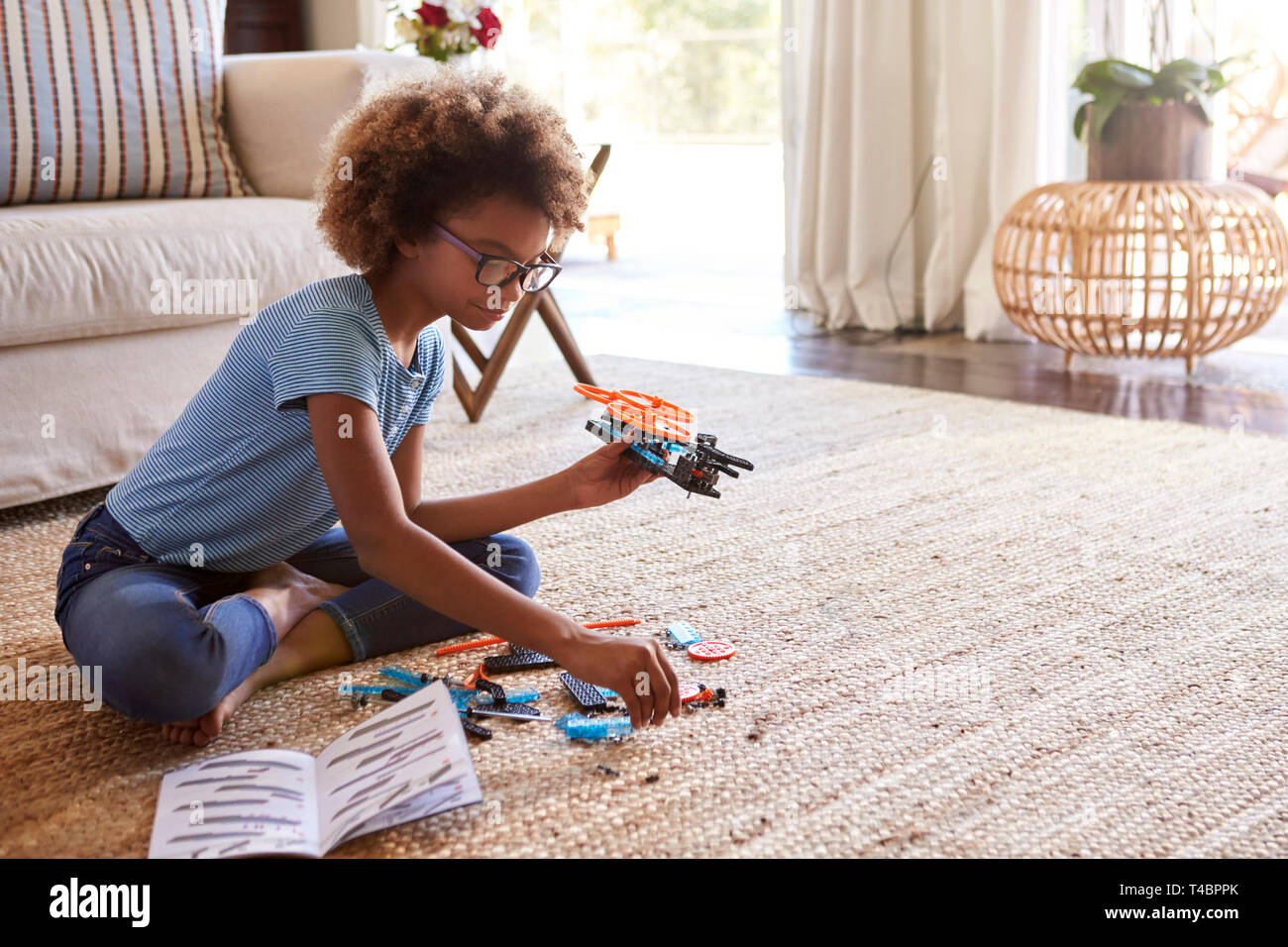 Pre-teen girl sitting on the floor in the living room building a toy from a construction kit, close up - Stock Image