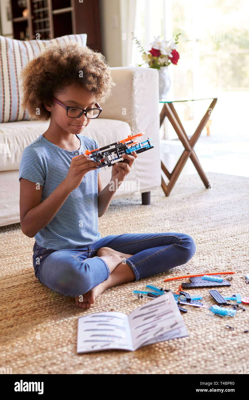 Pre-teen girl sitting on the floor in the living room building a toy from a construction kit, close up, vertical - Stock Image