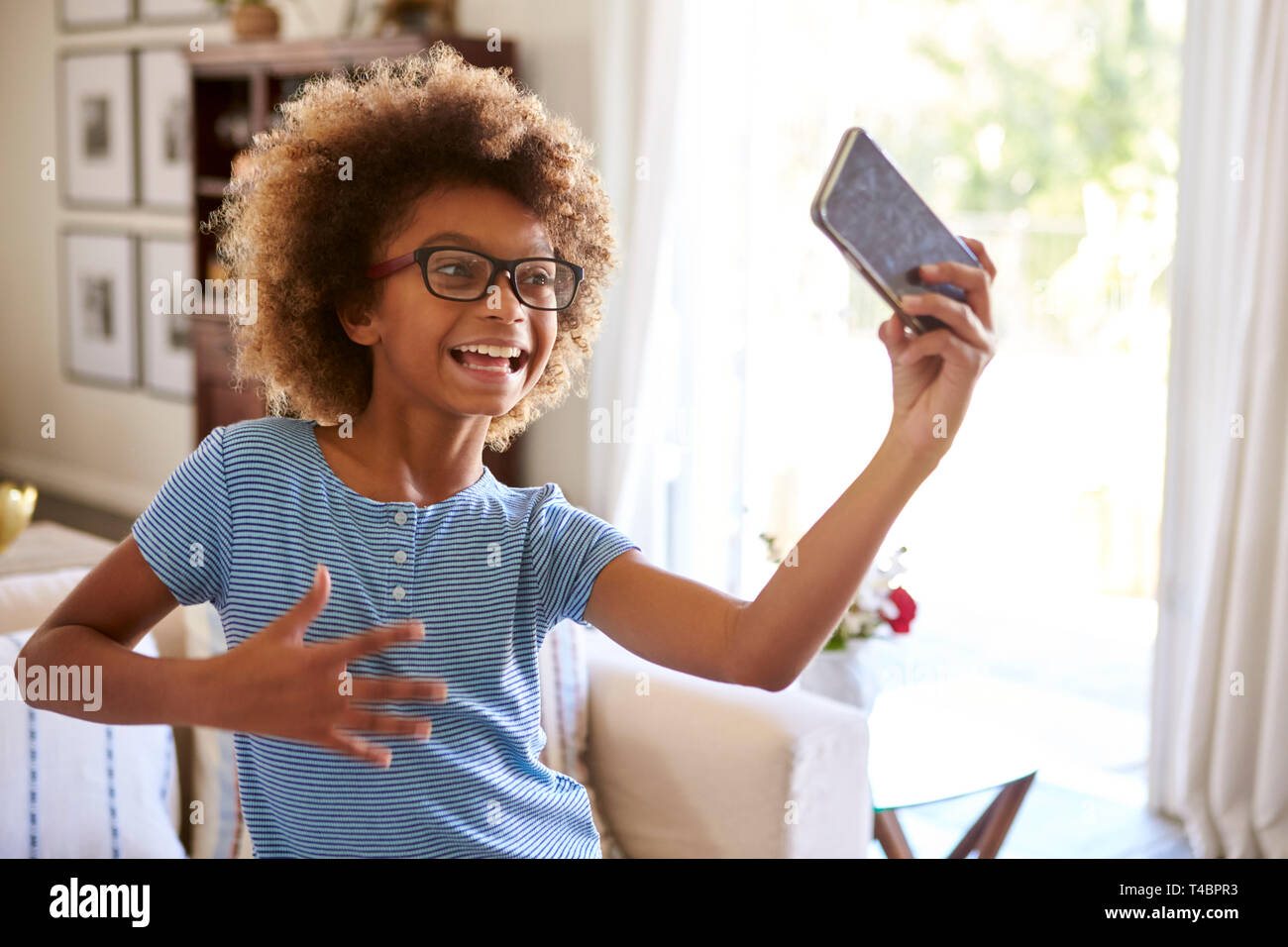 Pre-teen girl filming herself singing using a social media app on her smartphone, close up - Stock Image