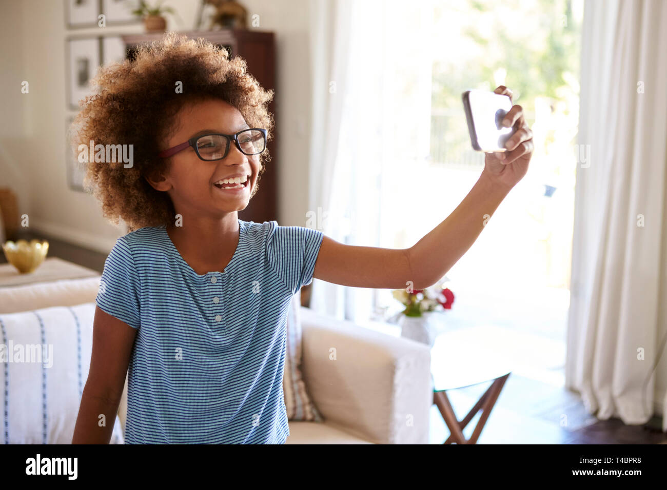 Pre-teen girl taking a selfie photo standing in the living room laughing, close up, focus on foreground - Stock Image