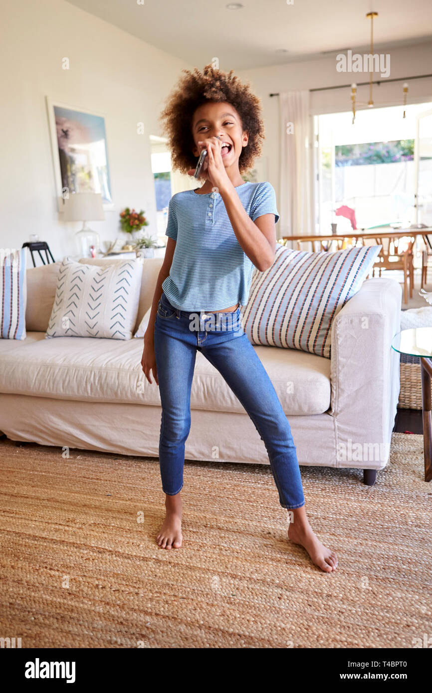 Pre-teen black girl dancing and singing in the living room at home using her phone as a microphone, full length, vertical - Stock Image