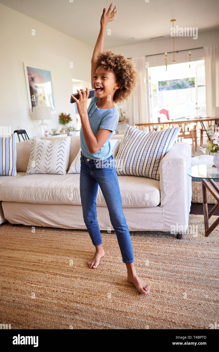 Pre-teen girl dancing and singing in the living room at home using her phone as a microphone, full length, vertical - Stock Image
