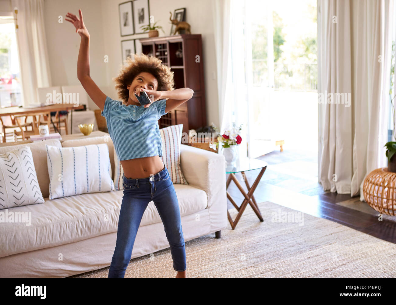 Pre-teen girl dancing and singing along to music in the living room at home using her phone as a microphone, three quarter length - Stock Image