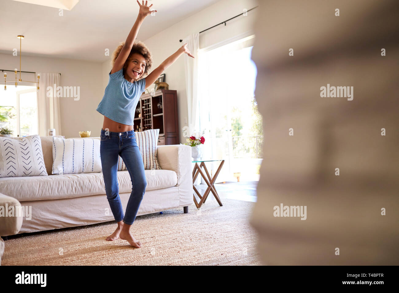 Pre-teen girl dancing and singing along to music on TV in the living room at home, three quarter length - Stock Image