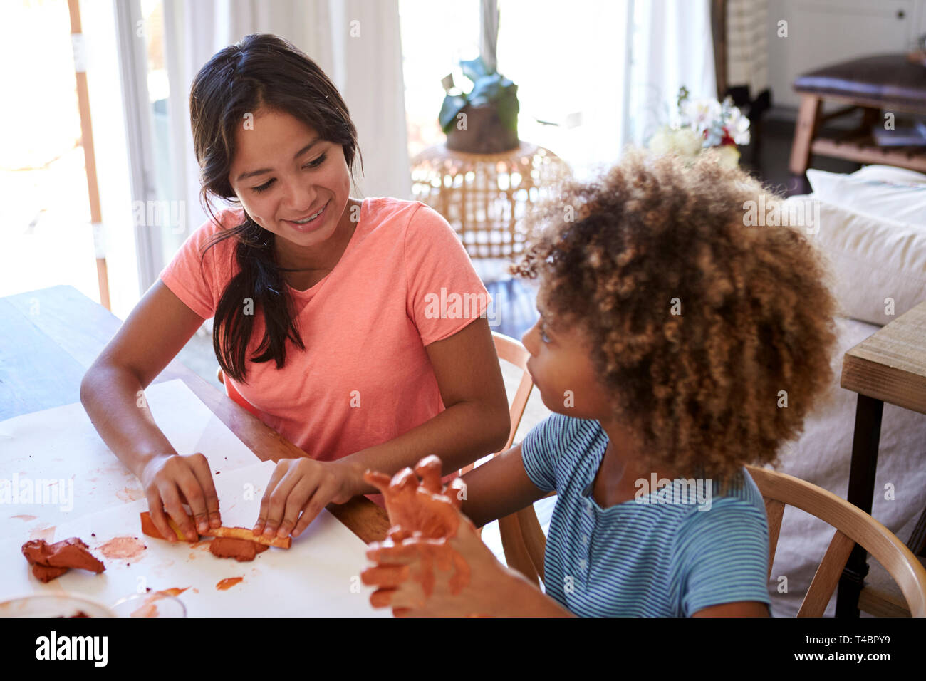 Two young teen and pre-teen girlfriends sitting at a table at home playing with modelling clay, close up, elevated view - Stock Image