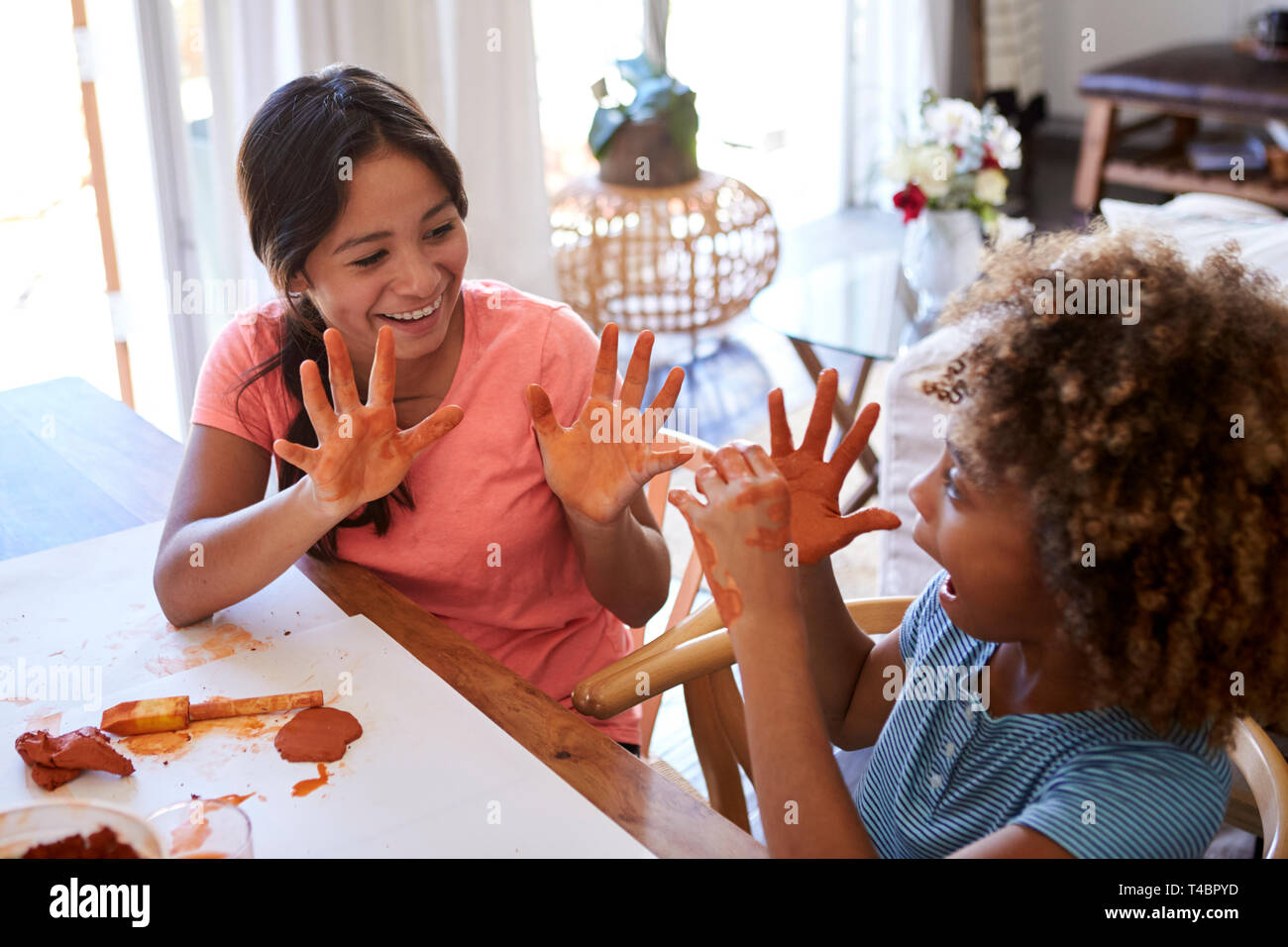 Two young teen and pre-teen girlfriends sitting at a table at home using modelling clay, showing each other their dirty hands, elevated view - Stock Image
