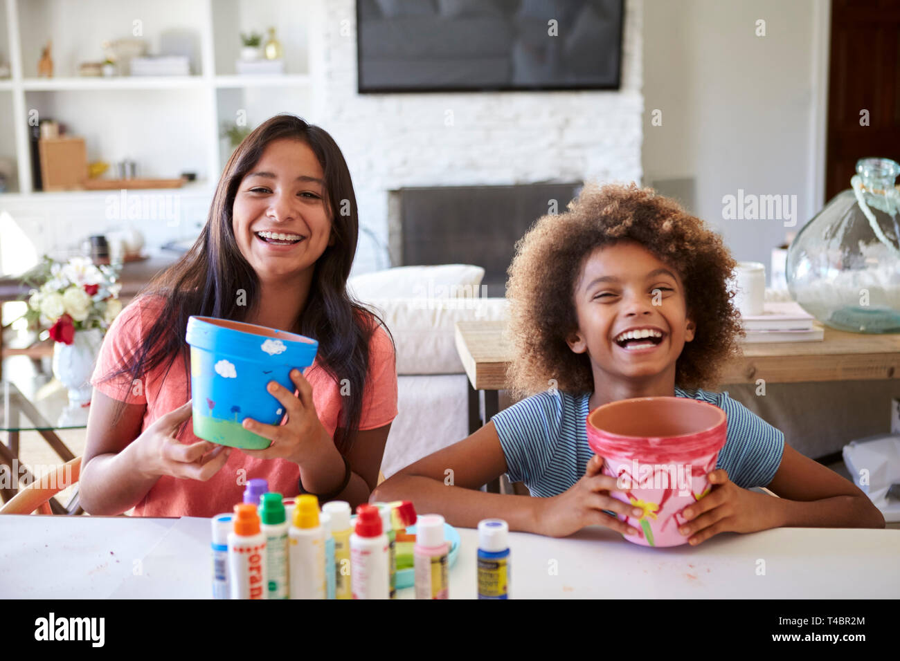 Happy pre-teen girl and her older girlfriend holding plant pots that they've decorated with paints at home, smiling to camera, close up - Stock Image