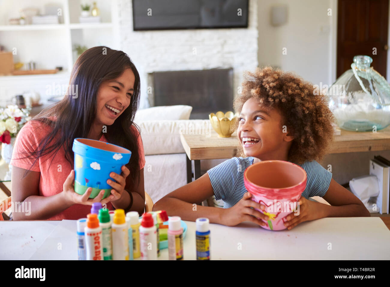 Happy pre-teen girl and her older girlfriend holding plant pots that they've decorated with paints at home, smiling at each other, close up - Stock Image