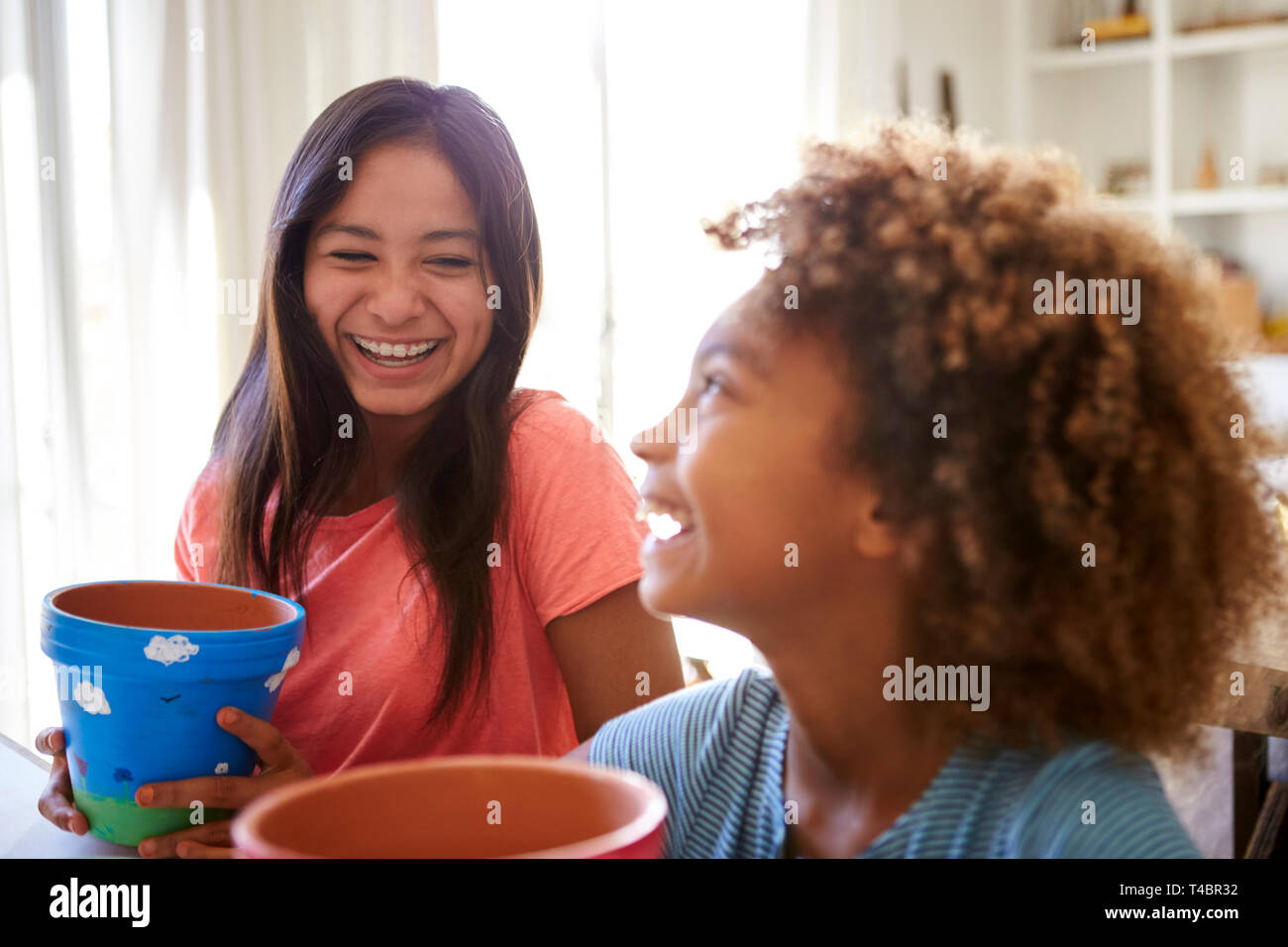 Laughing pre-teen girl and her older girlfriend holding plant pots that they've decorated with paints at home, selective focus, close up - Stock Image