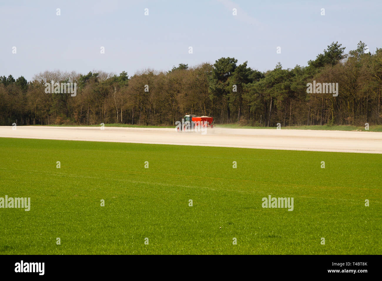 ROERMOND, NETHERLANDS - MARCH 30. 2019: Chalk fertilizer application by tractor with spreader to prepare the field for growing grass lawn - Stock Image