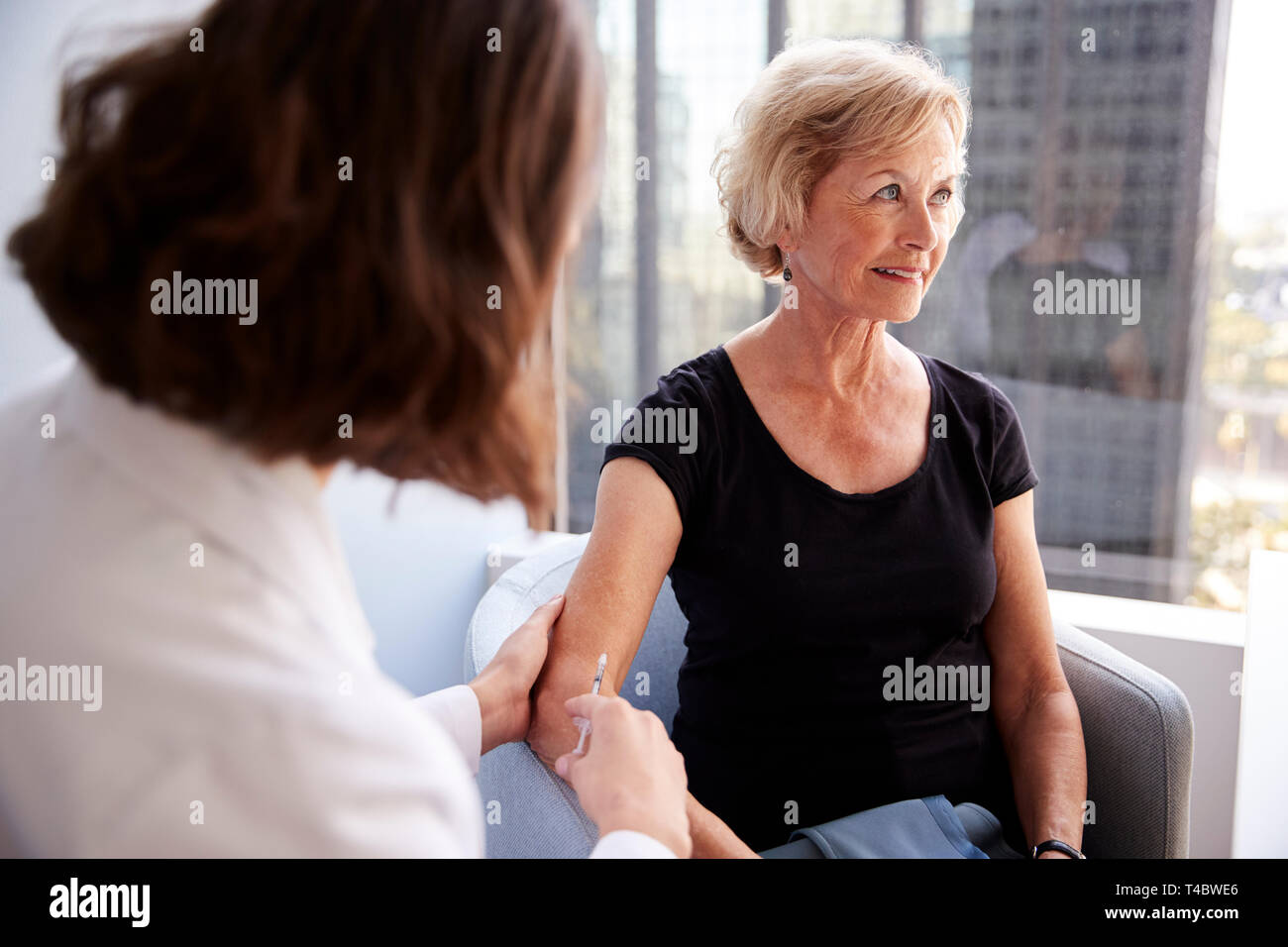 Senior Woman Being Vaccinated With Flu Jab By Female Doctor In Hospital Office - Stock Image