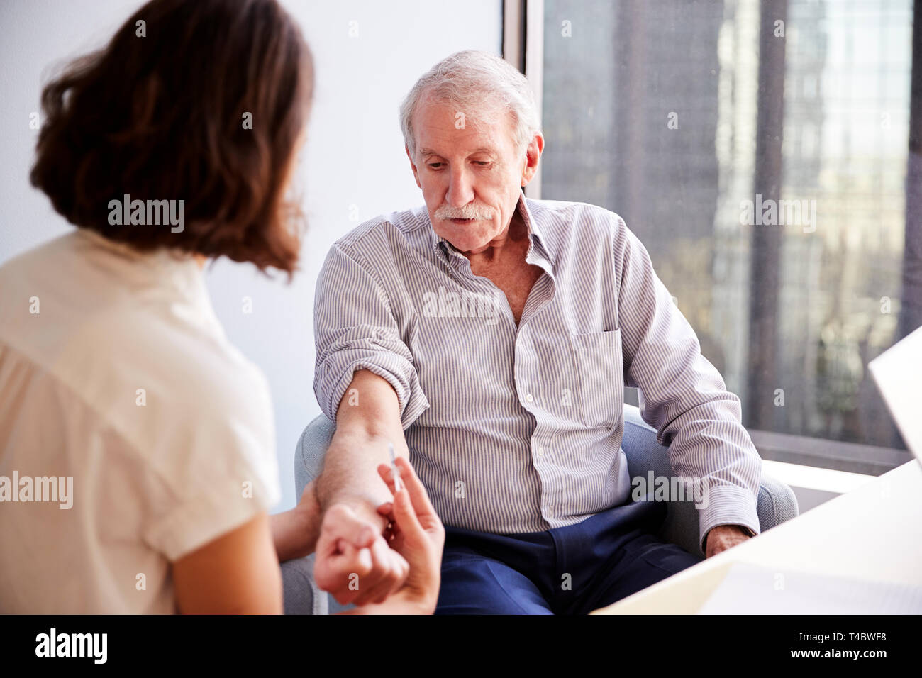 Senior Man Being Vaccinated With Flu Jab By Female Doctor In Hospital Office - Stock Image