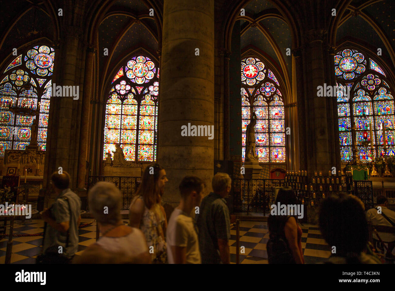 July 26, 2018 - Paris, France - Visitors enjoy the gothic architecture and stain glass windows in Notre-Dame Cathedral. Notre Dame de Paris (French for ''Our Lady of Paris'', meaning the church in Paris dedicated to Mary, the mother of Jesus), often known simply as Notre-Dame in English, is a gothic cathedral on the eastern half of the Ile de la Cite in Paris, France, with its main entrance to the west. While a major tourist destination, it is still used as a Roman Catholic cathedral (archbishopric of Paris). Notre Dame de Paris is widely considered the finest example of French gothic architec - Stock Image