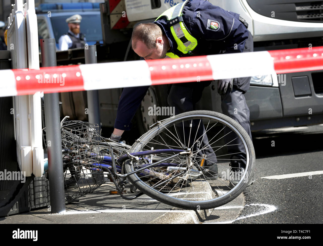 """16 April 2019, North Rhine-Westphalia, Düsseldorf: Behind a barrier tape with the inscription """"Police barrier"""", a bicycle is lying in front of a truck at the scene of the accident. There has been an accident with a truck (in the back) and a cyclist in downtown Düsseldorf. More precise circumstances regarding the cause of the accident are not yet known. Photo: Martin Gerten/dpa Stock Photo"""