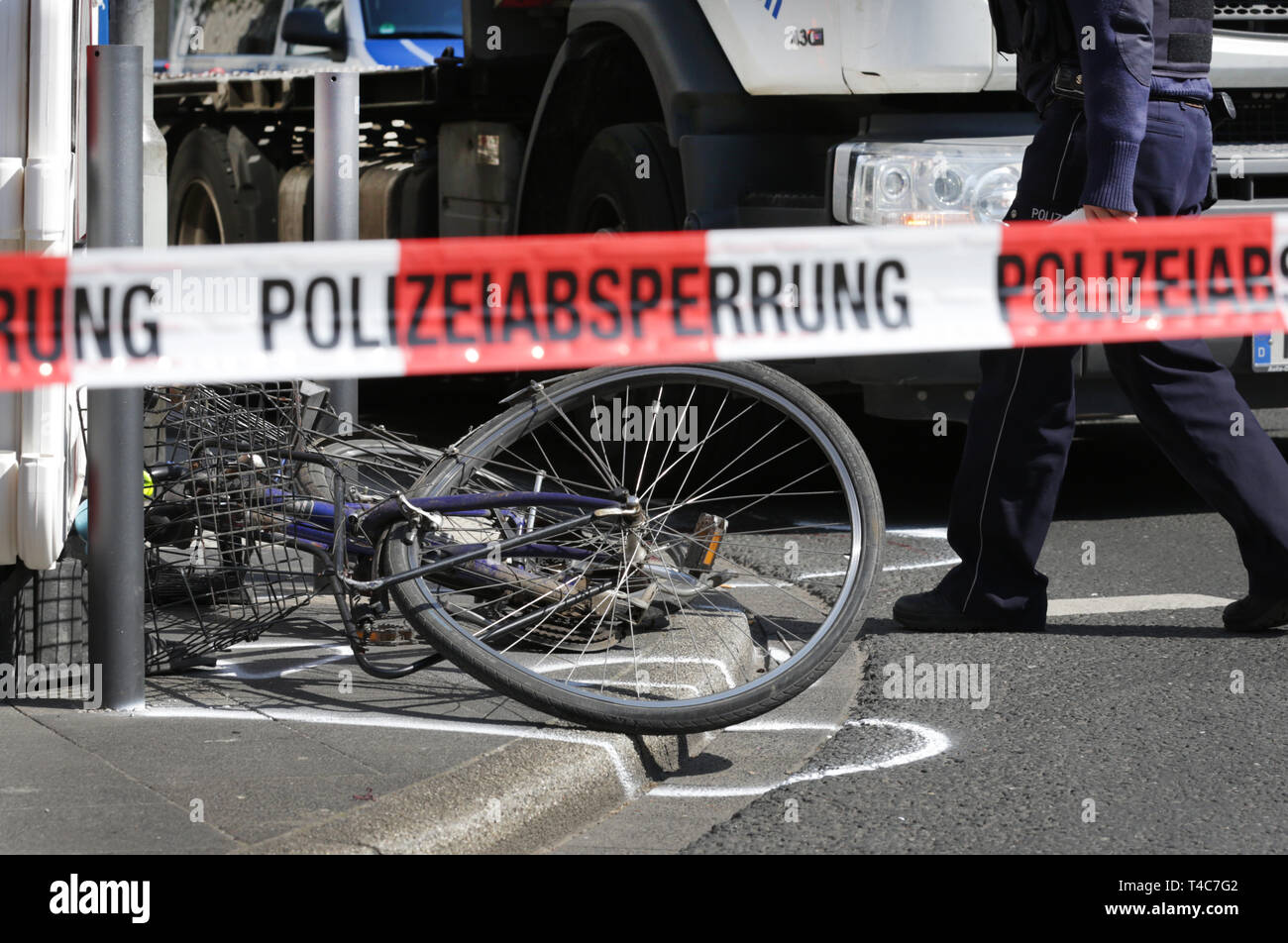 "16 April 2019, North Rhine-Westphalia, Düsseldorf: Behind a barrier tape with the inscription ""Police barrier"", a bicycle is lying in front of a truck at the scene of the accident. There has been an accident with a truck (in the back) and a cyclist in downtown Düsseldorf. More precise circumstances regarding the cause of the accident are not yet known. Photo: Martin Gerten/dpa Stock Photo"