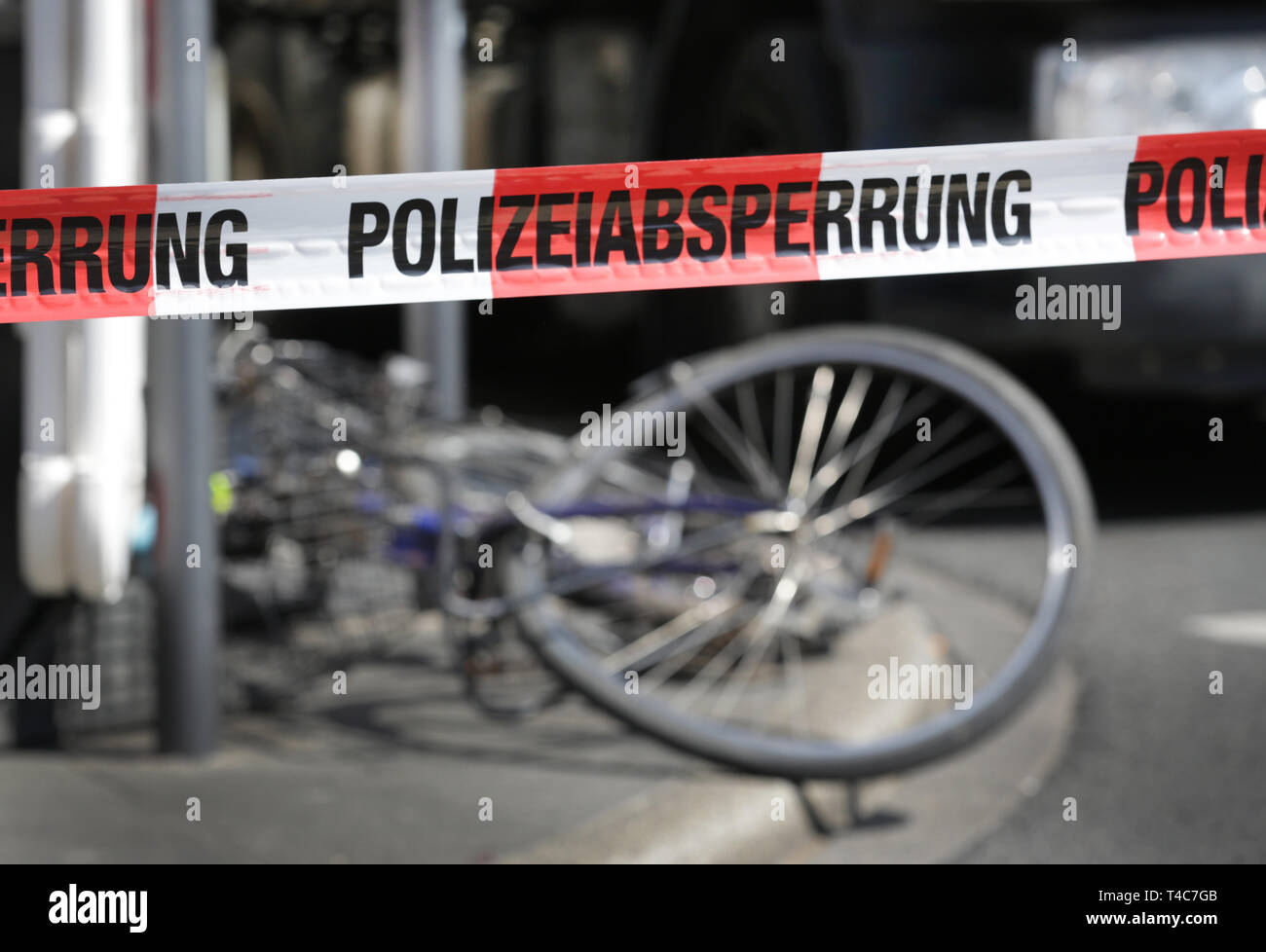 """16 April 2019, North Rhine-Westphalia, Düsseldorf: Behind a barrier tape with the inscription """"Police barrier"""" there is a bicycle in front of a truck at the scene of the accident. There has been an accident with a truck (in the back) and a cyclist in downtown Düsseldorf. More precise circumstances regarding the cause of the accident are not yet known. Photo: Martin Gerten/dpa Stock Photo"""