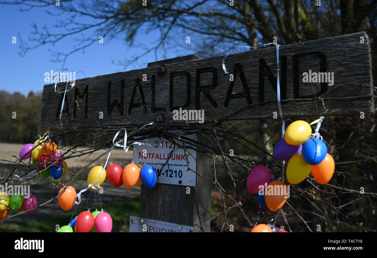 """16 April 2019, Lower Saxony, Ostereistedt: Colourful Easter eggs hang from the sign """"Am Waldrand"""", which leads to the house of """"Hanni Hase"""" in the forest near Ostereistedt. Here children from all over the world send letters to Hanni Hase at Easter, which are then answered at the post office in Zeven. Photo: Carmen Jaspersen/dpa Stock Photo"""