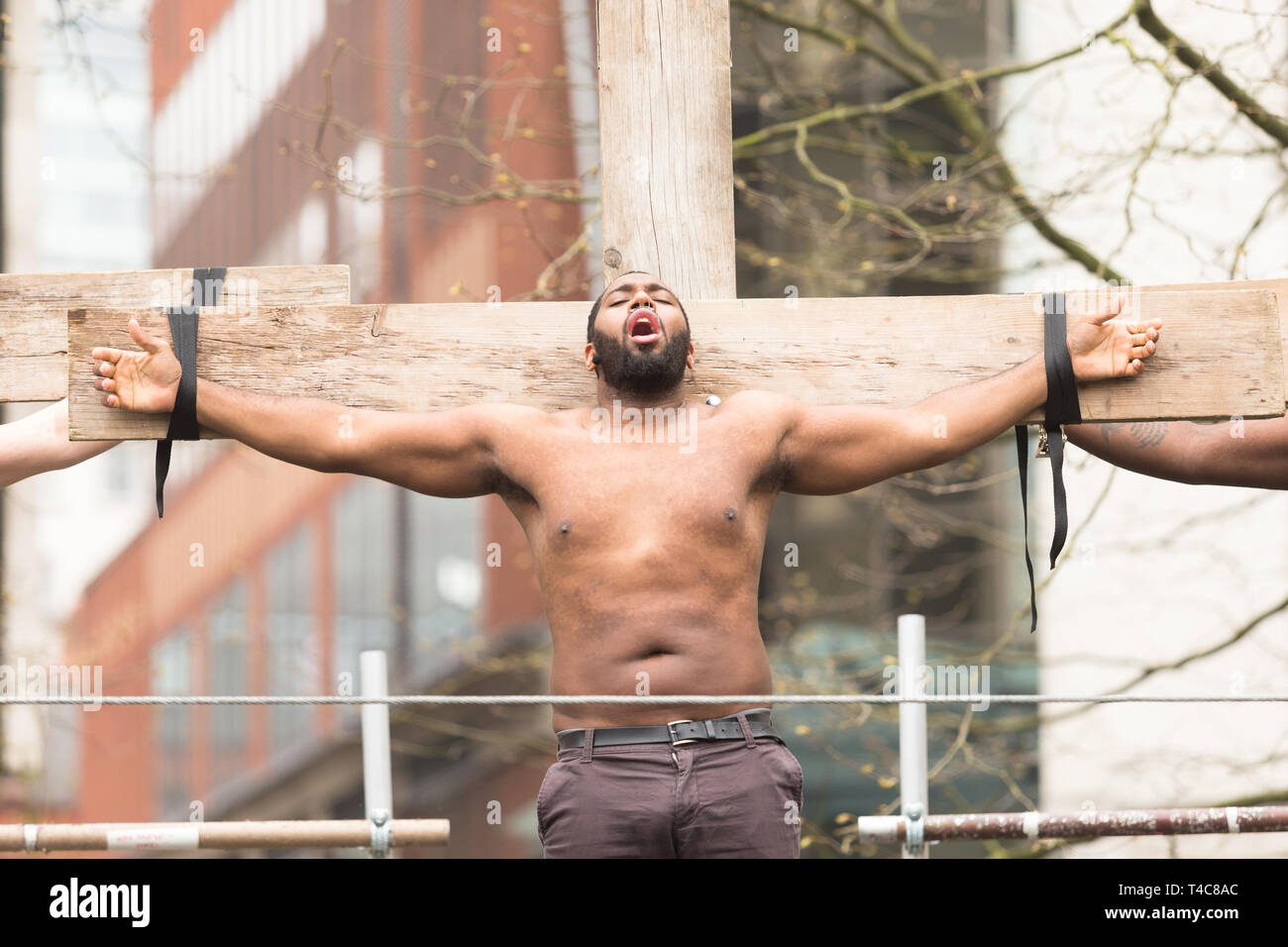Birmingham, UK. 16th April, 2019. A contemporary Christ-figure is crucified. A diverse team of one hundred community actors, musicians and stewards alongside Saltine Theatre Company re-tell the Easter story in a live procession through Birmingham city centre. The procession finishes up at St. Philip's Cathedral  Peter Lopeman/Alamy Live News Stock Photo