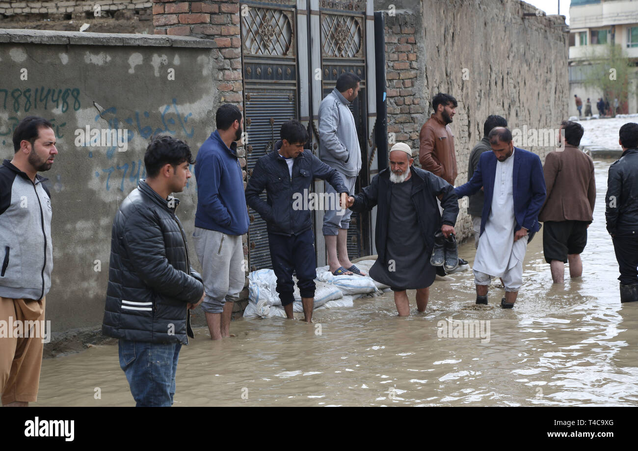 Kabul, Afghanistan. 16th Apr, 2019. People leave their houses surrounded by flood in Kabul, capital of Afghanistan, April 16, 2019. One person has been reported dead after the Kabul river flooded in the country's capital, where the government issued a warning asking people to leave flood-prone areas and houses located at the two banks of the river, as the rising overflow was uncontrollable. Credit: Rahmat Alizadah/Xinhua/Alamy Live News - Stock Image