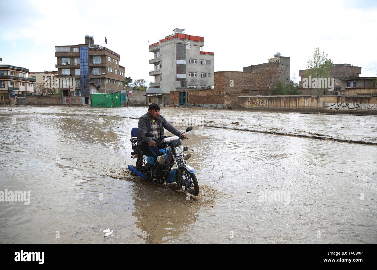 Kabul, Afghanistan. 16th Apr, 2019. An Afghan man rides his motorcycle in flood in Kabul, capital of Afghanistan, April 16, 2019. One person has been reported dead after the Kabul river flooded in the country's capital, where the government issued a warning asking people to leave flood-prone areas and houses located at the two banks of the river, as the rising overflow was uncontrollable. Credit: Rahmat Alizadah/Xinhua/Alamy Live News - Stock Image