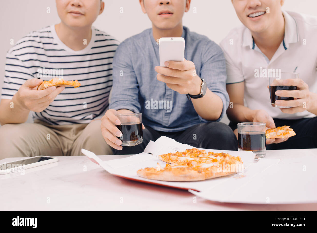 Group of friends eating pizza and watching tv - Stock Image