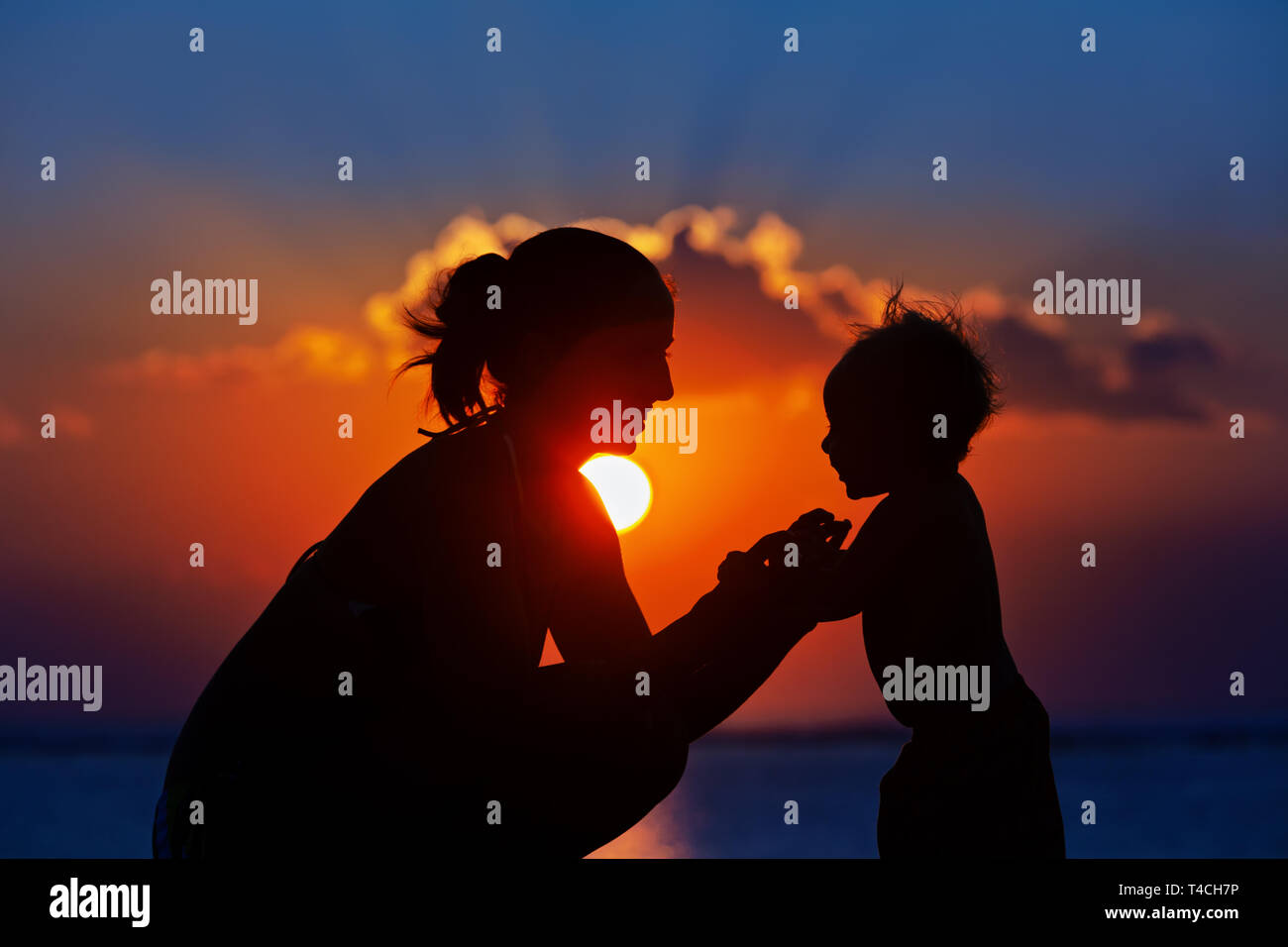 Happy family black silhouette on sunset sky background. Young mother, baby son have fun together, walk by sea beach. Barefoot child look at sun. - Stock Image