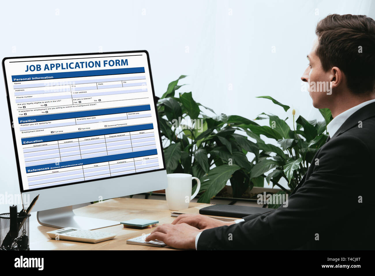 man in suit filling in Job Application Form, Employment Career Concept Stock Photo