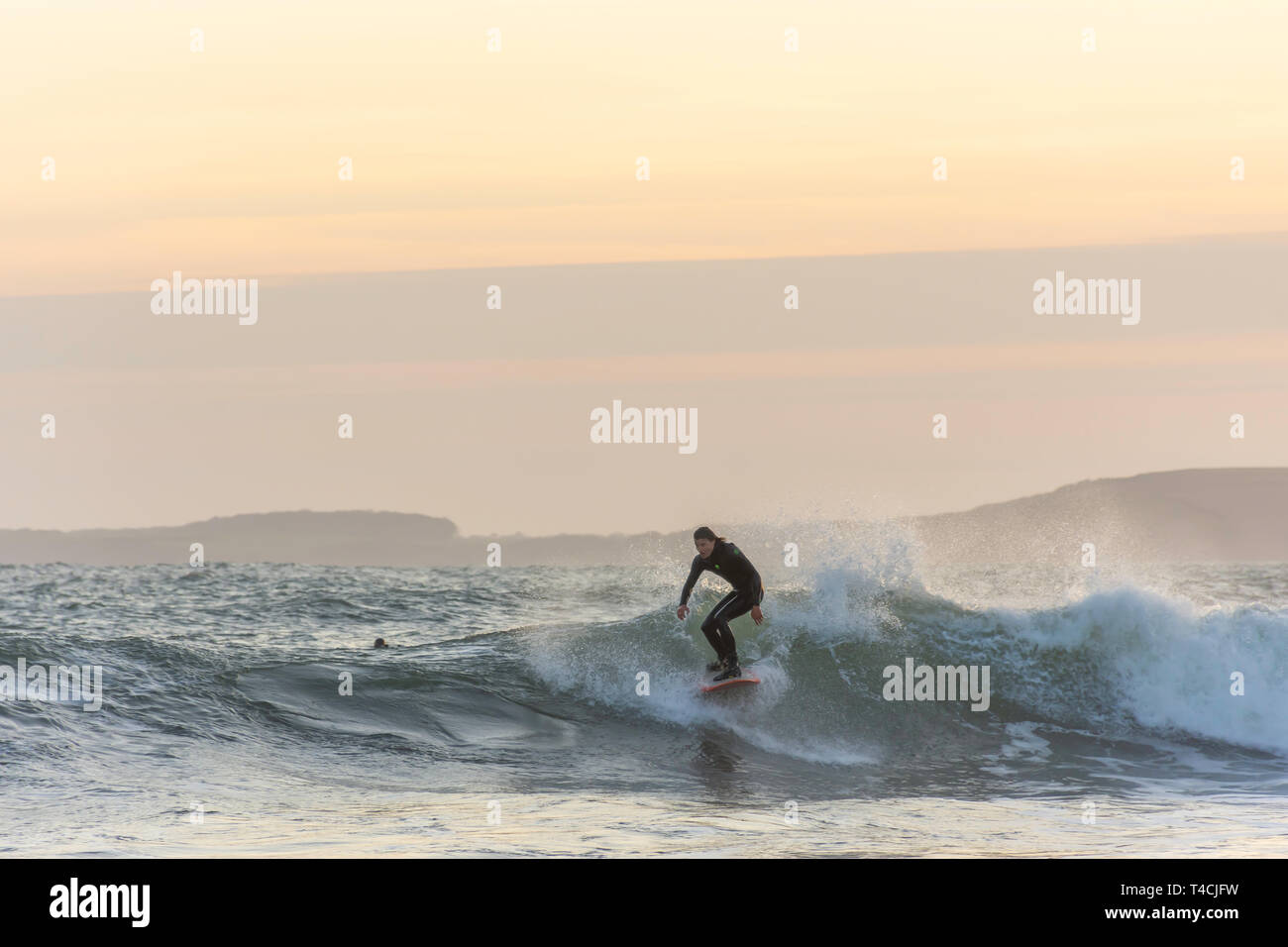 Tenby, Pembrokeshire/UK.04.18.2018-Surfer riding the wave in rough sea at sunset.Healthy, active lifestyle, extreme sport.Recreational pursuit. - Stock Image