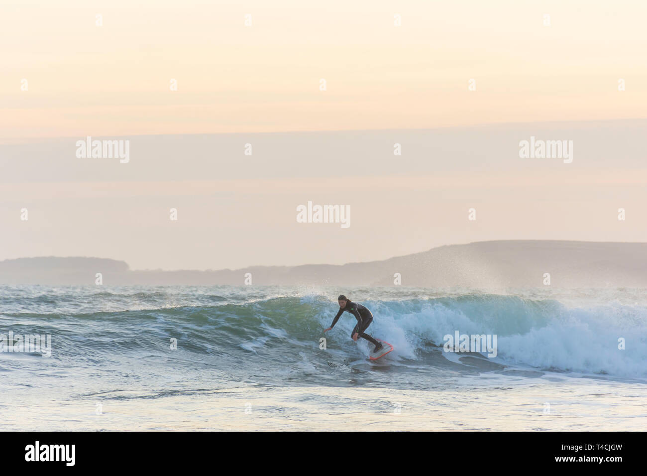 Tenby, Pembrokeshire/UK.04.18.2018-Surfer riding the wave in rough sea during sunset.Healthy, active lifestyle, extreme sport.Recreational pursuit. - Stock Image