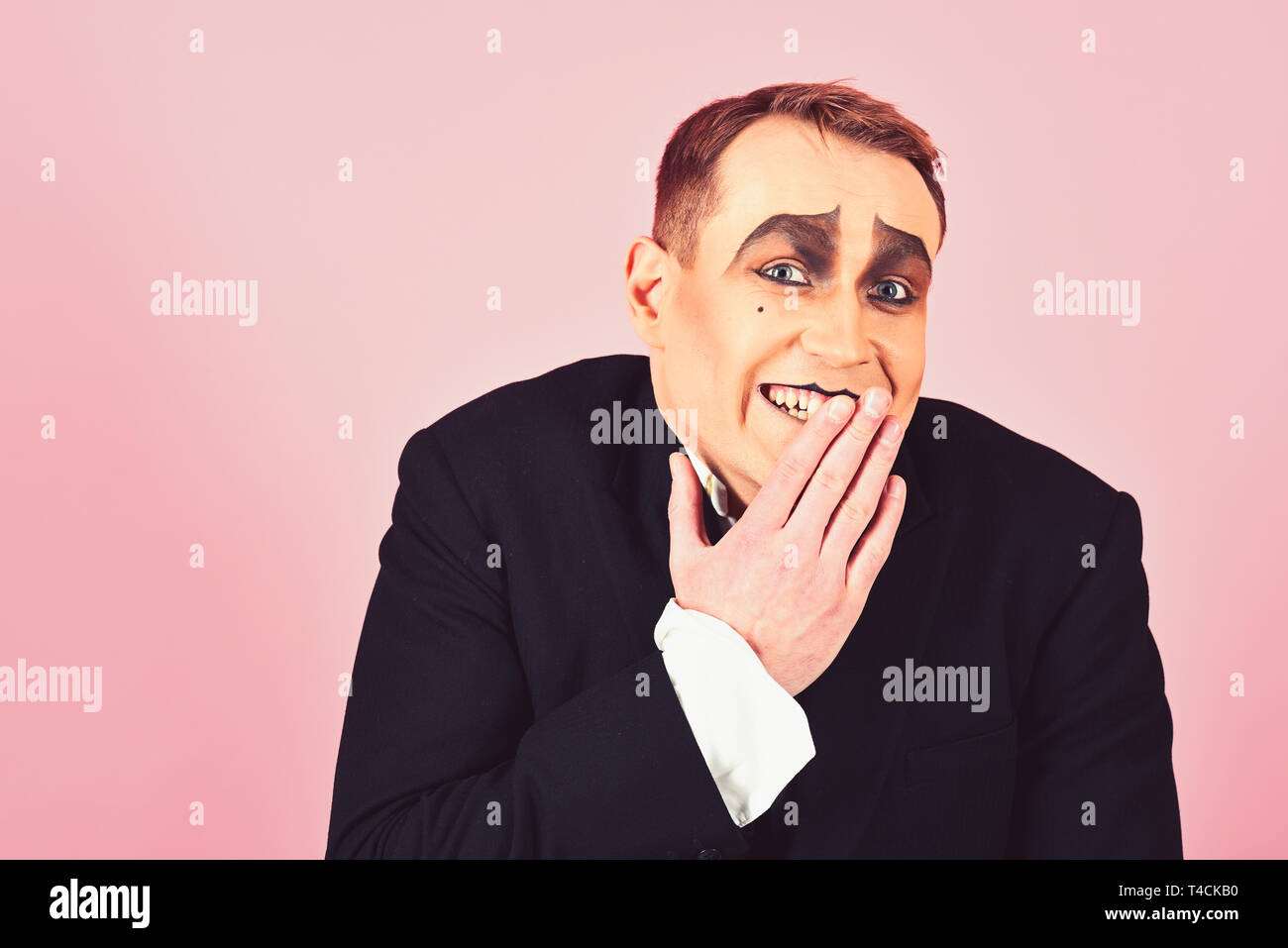 Laughing face. Comedian performer giggling. Mime artist. Mime with face paint. Man with mime makeup. Theatre actor miming. Stage actor miming - Stock Image